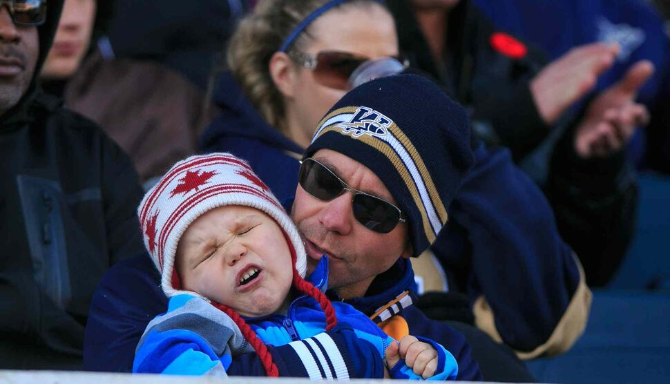 Keith Tarr calms his three-year-old son Jaxon near the end of another Blue Bombers loss at Investors Group Field. (Melissa Tait / Winnipeg Free Press)