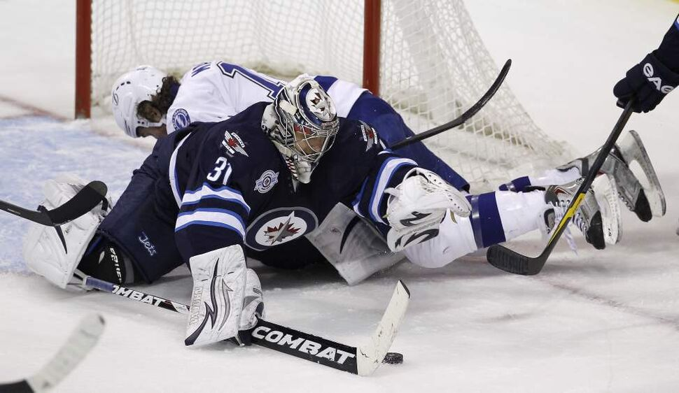 Winnipeg Jets' goaltender Ondrej Pavelec (31) is run over by Tampa Bay Lightning's Ryan Malone (12) during first period NHL action at MTS Centre in Winnipeg, Saturday, April 7, 2012. (TREVOR HAGAN/WINNIPEG FREE PRESS)
