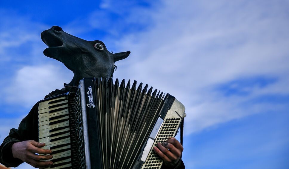 A busker named Blaine plays an accordion while wearing a horse head outside the MLCC in Osborne Village Monday evening.  (Melissa Tait / Winnipeg Free Press)