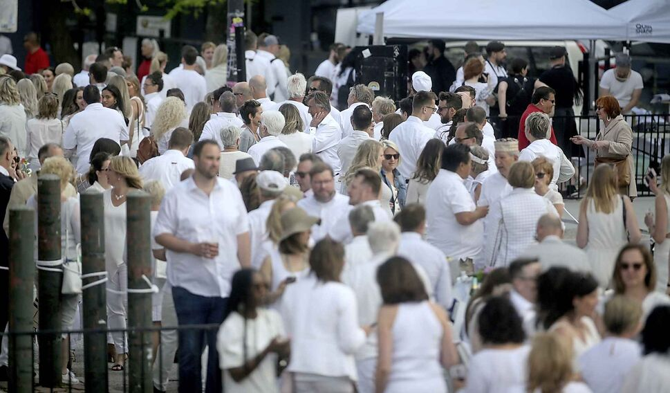 Guests arrive and mingle in a sea of white.</p>