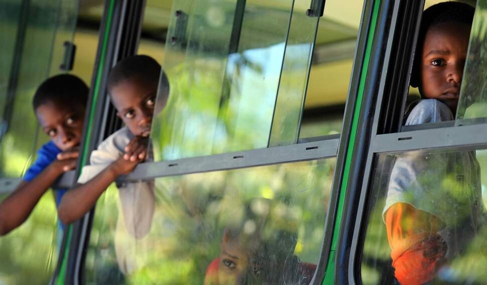 School children look out the window of a classroom bus at the Plas Timoune school for earthquake-traumatized children in Port-au-Prince, Haiti. The school consists of five buses donated by the Dominican Republic after the earthquake on January 12, 2010. (Ricky Carioti / Washington Post)