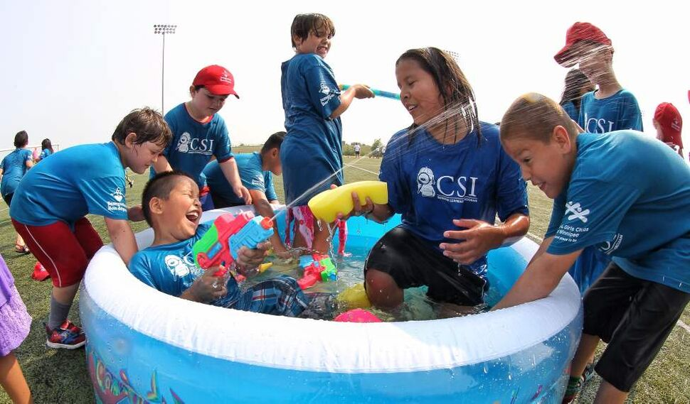 Kids from the West Grove Community School Investigators Summer Learning Program jump at the chance to have a water fight as almost 1000 kids in the CSI program gathered at the Waverley Soccer Complex for the first Jumpstart Games.  July 31, 2014  (Mike Deal / Winnipeg Free Press)