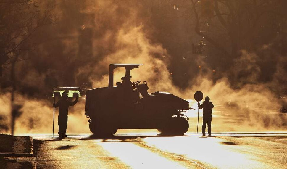 Steam rises off new asphalt being installed on Balmoral Street at Cumberland Avenue. October 19, 2014  (Mike Deal / Winnipeg Free Press)