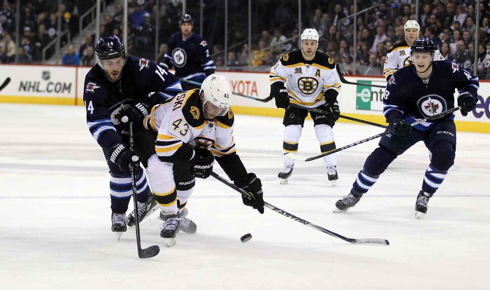 Jets' Anthony Peluso and Bruins' Matt Bartkowski trip each other up as they follow the puck over the Boston blue line during the second period of Thursday's game. (Phil Hossack / Winnipeg Free Press)