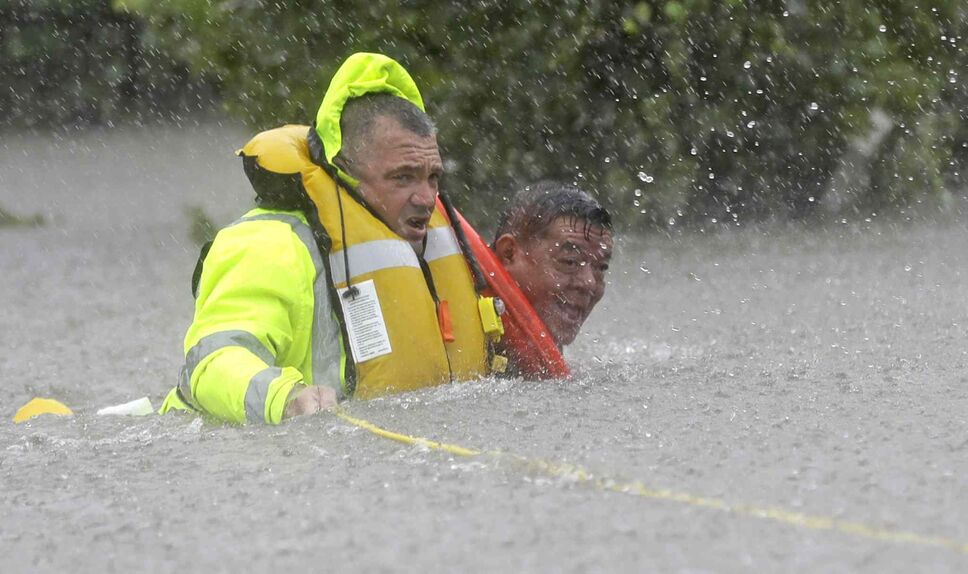 Wilford Martinez, right, is rescued from his flooded car by Harris County Sheriff's Department Richard Wagner along Interstate 610 in floodwaters from Tropical Storm Harvey on Sunday, Aug. 27, 2017, in Houston, Texas.  (David J. Phillip / The Associated Press)