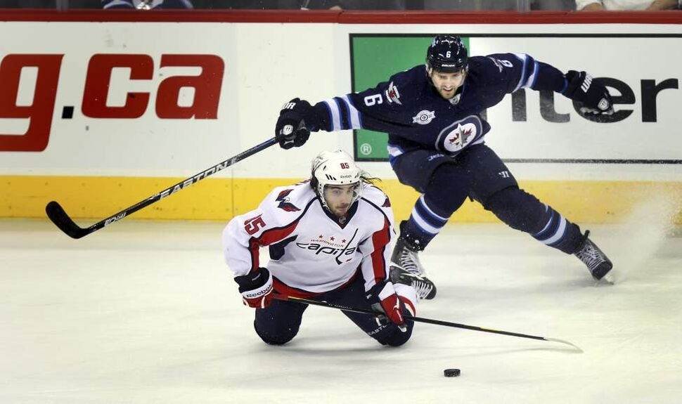 Winnipeg Jets' Ron Hainsey swoops over Washington Capitals' Mathieu Perreault deep in the Jets zone.  December 15, 2011 (Phil Hossack / Winnipeg Free Press)