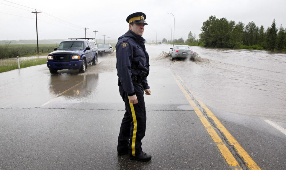 Cst. Ian Gillard driects traffic through a flooded intersection near Bragg Creek, Alta. (Jeff McIntosh / The Canadian Press)