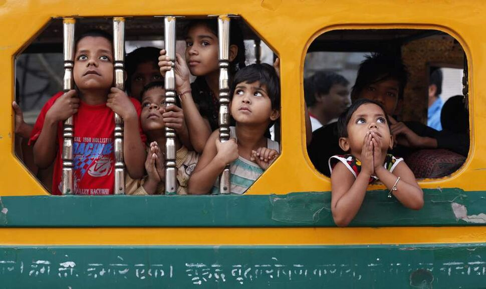 Indian children watch a Dussehra festival procession early morning in Allahabad, India, Sunday, Oct. 21, 2012. The Hindu festival Dussehra commemorates the triumph of Lord Rama over the demon king Ravana, marking the victory of good over evil. (AP Photo/Rajesh Kumar Singh)