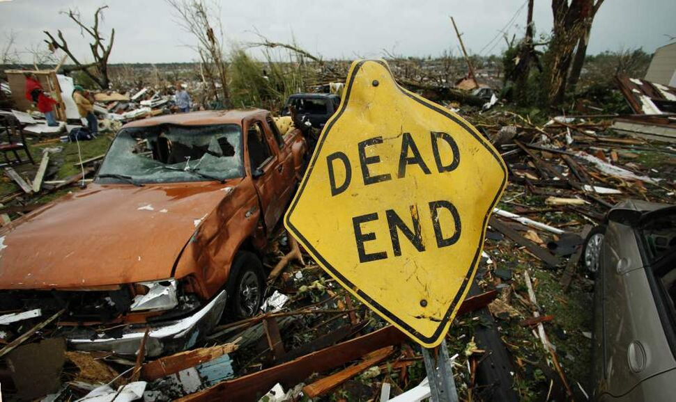 A mangled street sign stands among tornado debris in Joplin, Mo., Monday, May 23, 2011. A large tornado moved through much of the city Sunday, damaging a hospital and hundreds of homes and businesses and killing at least 116 people. (AP Photo/Charlie Riedel) (CP)
