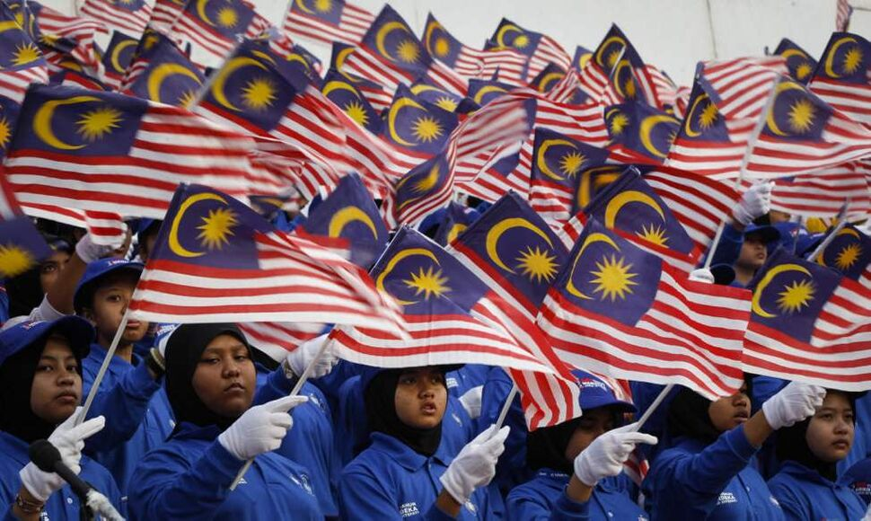 Malaysian students wave their national flags at rehearsal for Malaysia National Day celebrations at Independence Square in Kuala Lumpur, Malaysia. The country will celebrate its 55th National Day on Aug. 31. (AP Photo/Vincent Thian)