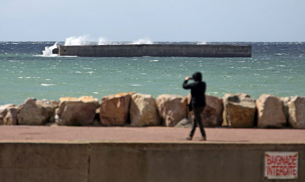 "A visitor takes snapshots of the remains of the artificial harbour of Arromanches in western France. The harbour, known as ""Port Winston"", whose remains continue to remind visitors of the remarkable technical feat of taking 600,000 tonnes of concrete across the Channel in wartime to serve as a base for Allied troops.  (Remy de la Mauviniere / The Associated Press )"