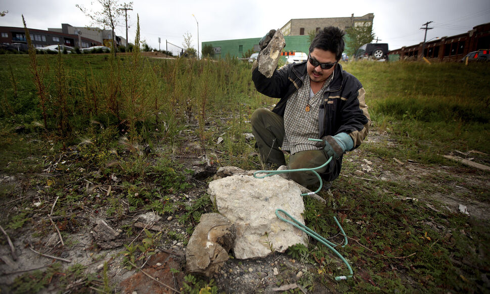 A volunteer, who drove 'in from the east' and didn't want to give his name, fashions a grappling hook out of reinforcing bar along the Red River near the Alexander Docks. September 17, 2014  (Phil Hossack / Winnipeg Free Press)