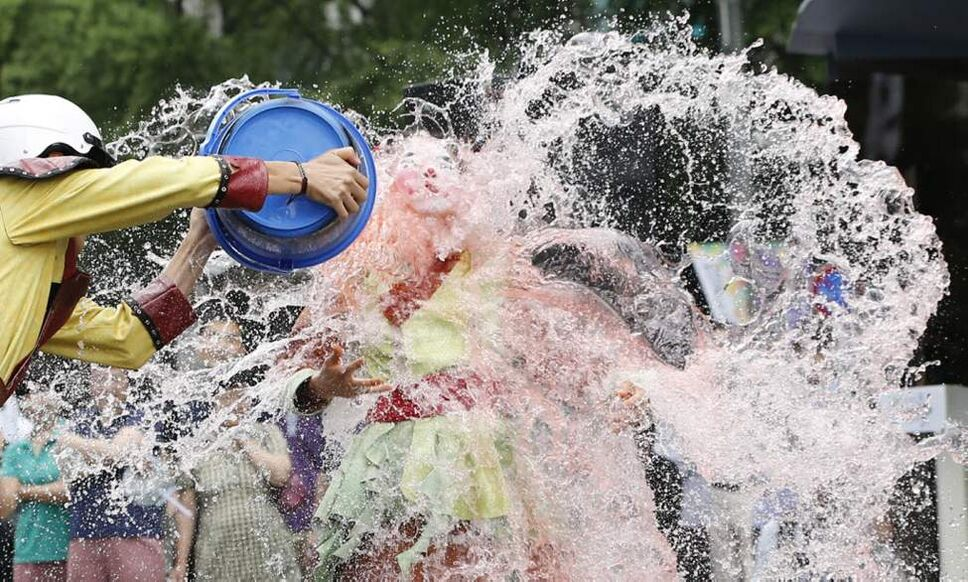 A man splashes a bucket of water on participants of a water festival in Seoul, South Korea. The event promotes tourism of local county offices ahead of summer vacation season. (AP Photo/Lee Jin-man)