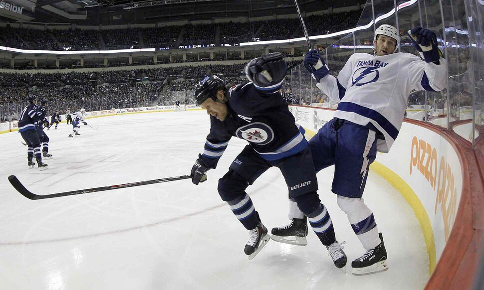 Winnipeg Jets' Olli Jokinen (12) hits Tampa Bay Lightning's Eric Brewer (2) during the second period.  (Trevor Hagan / The Canadian Press)