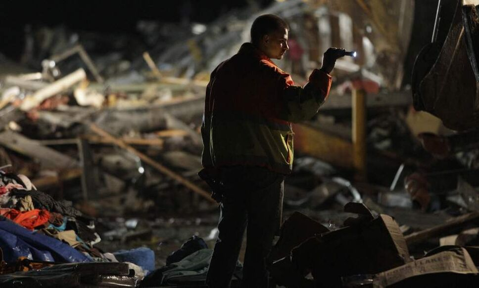 An emergency worker searches a Walmart store that was severely damaged by a tornado in Joplin, Mo., Sunday. (Charlie Riedel / The Associated Press)