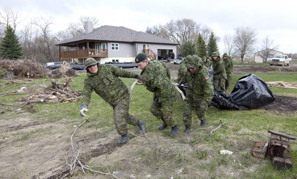 Members of the Canadian Forces surround a home with a water dike close to the Hoop and Holler Bend near Portage La Prairie, Man, Thursday, May 12, 2011. Excavators were digging out a dike holding back the Assiniboine River even as the government continued Thursday to push back a decision to purposely flood homes and farmland in southern Manitoba.  May 12, 2011(THE CANADIAN PRESS/Jonathan Hayward)