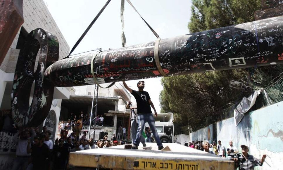 """Palestinians put a huge key on a truck, know as """"the key of return,"""" which was exhibited at the seventh Berlin Biennale, in the West Bank refugee camp of Aida near Bethlehem. The key symbolizes what the Palestinians call their """"right of return"""" to properties lost during the 1948 war surrounding Israel's creation. (AP Photo/Nasser Shiyoukhi)"""