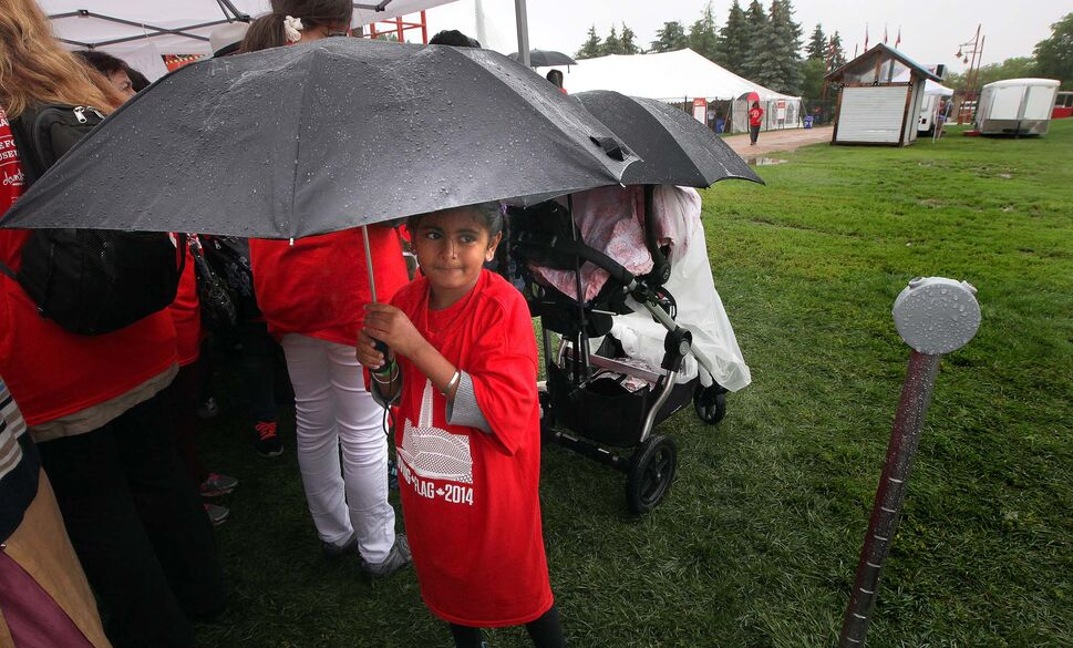 A young participant waits under an umbrella to participate in the living flag. (Phil Hossack / Winnipeg Free Press)