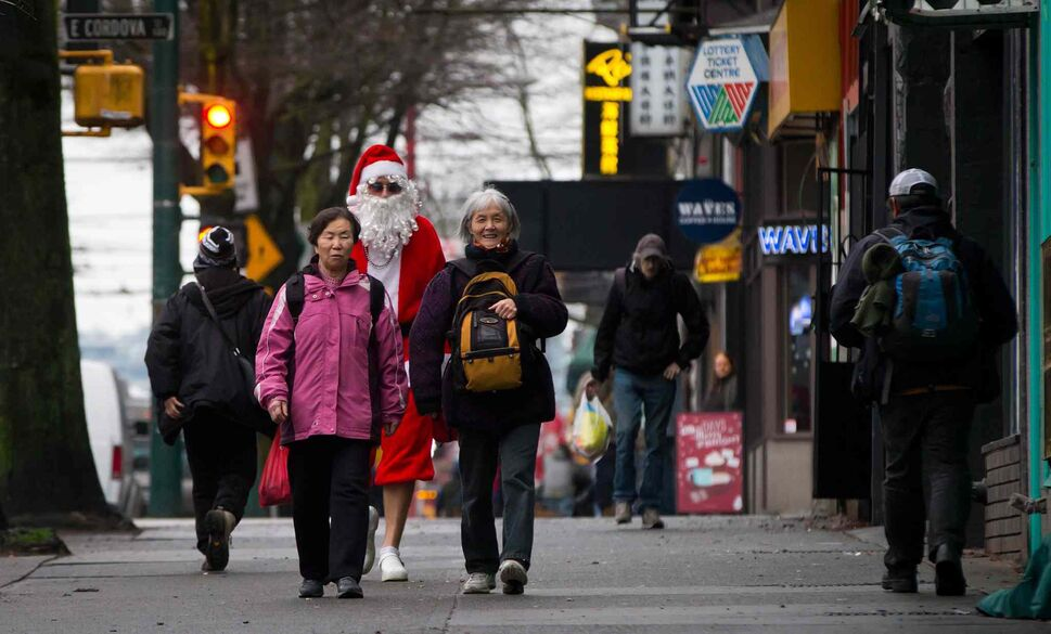 In a scene somehow reminiscent of 'Saturday Night Fever,' a man dressed as Santa Claus walks to a Santacon event in Vancouver's Downtown Eastside on Saturday. (DARRYL DYCK / THE CANADIAN PRESS)