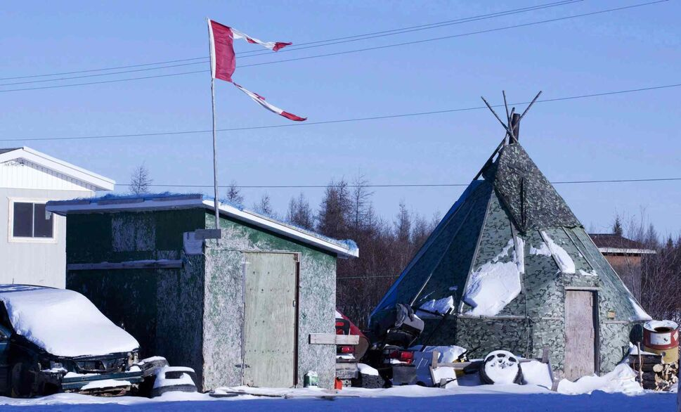 A tattered Canadian flag flies over a building in Attawapiskat, Ont. (CP)