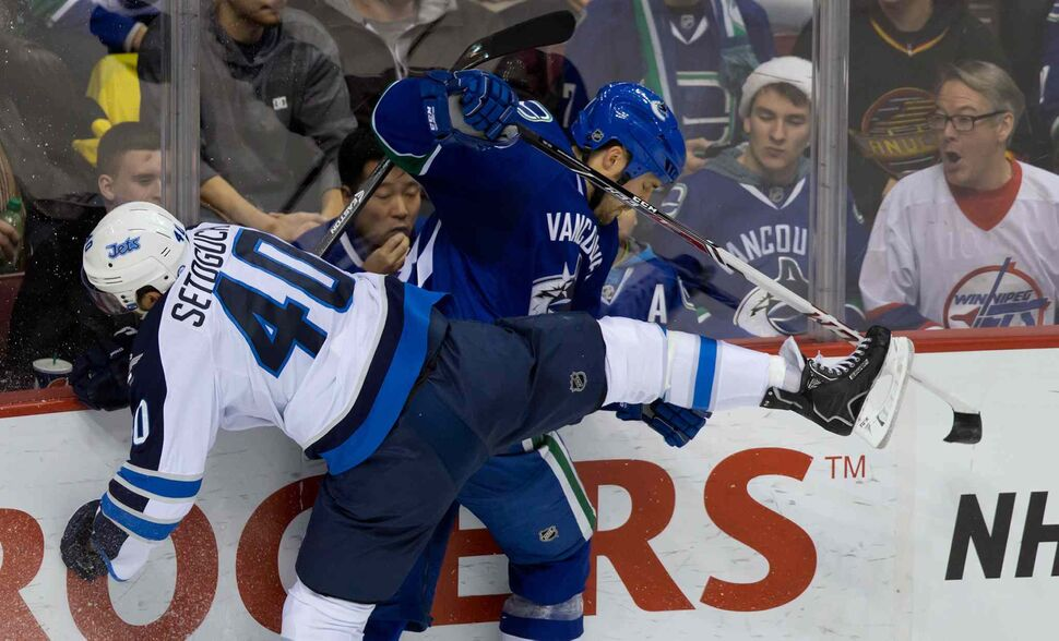 Winnipeg Jets forward Devin Setoguchi (left) and Vancouver Canucks' Andrew Alberts collide during the second period. (DARRYL DYCK / THE CANADIAN PRESS)