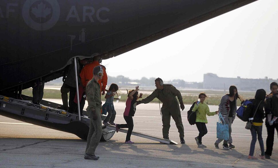 Northern Manitoba fire evacuees step off of a Canadian Forces C130 Herculese transport arrives at James Richardson International Airport in Winnipeg. (PHIL HOSSACK / WINNIPEG FREE PRESS)