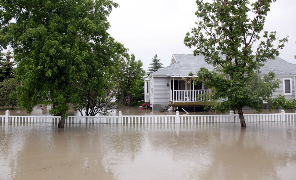 A property sits underwater in High River, Alta. (Jeff McIntosh / The Canadian Press)