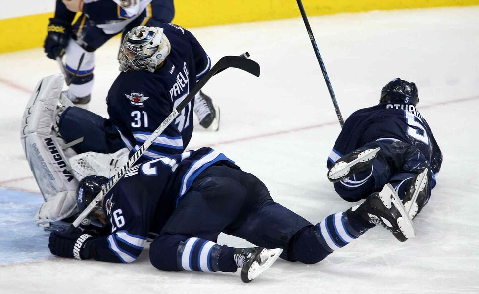 Winnipeg Jets goaltender Ondrej Pavelec falls onto teammate Blake Wheeler as defenceman Mark Stuart lays on the ice nearby during the third period. (TREVOR HAGAN / THE CANADIAN PRESS)