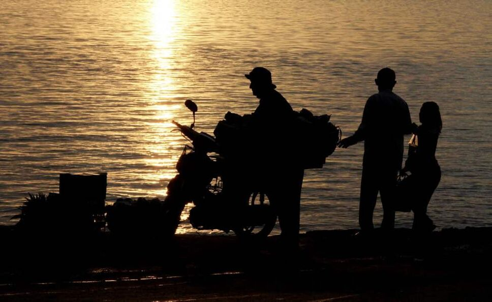 A man loads up lemon grasses in his motorcycle near a couple strolling on the river bank in the Mekong river in Phnom Penh, Cambodia. (AP Photo/Heng Sinith)