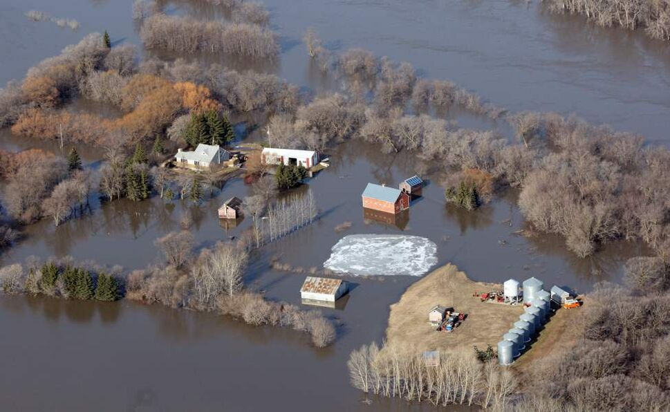 Farmers properties are surrounded by the flooded Red River near the town of St Jean Baptiste. JOE BRYKSA/WINNIPEG FREE PRESS