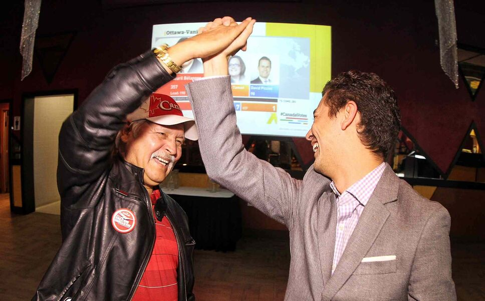 Volunteers for Robert Falcon Oullette, Liberal candidate for Winnipeg Centre, Albert Ratt (left) and Michael Sugawara (right) high-five as positive numbers come in for the Liberals across the country during the final moments of the federal election at the Canad Inns Polo Park Monday evening.  (Mike Deal / Winnipeg Free Press)
