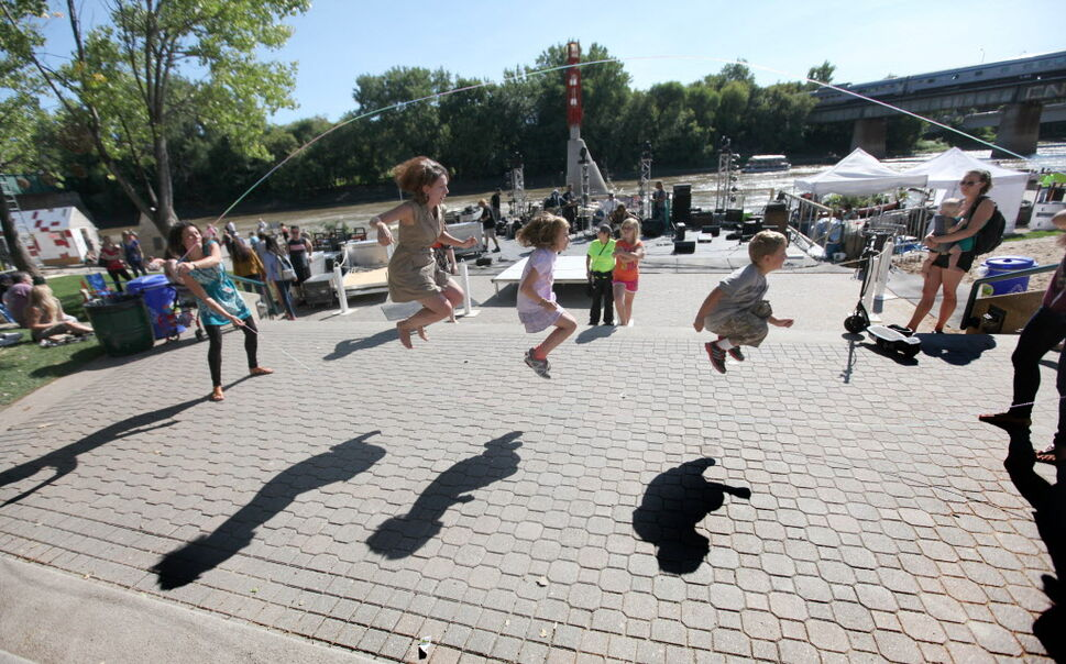 People gather along the waterfront at the Forks Saturday to play games and watch performances during the Prairie Barge Festival.  (Ruth Bonneville / Winnipeg Free Press )