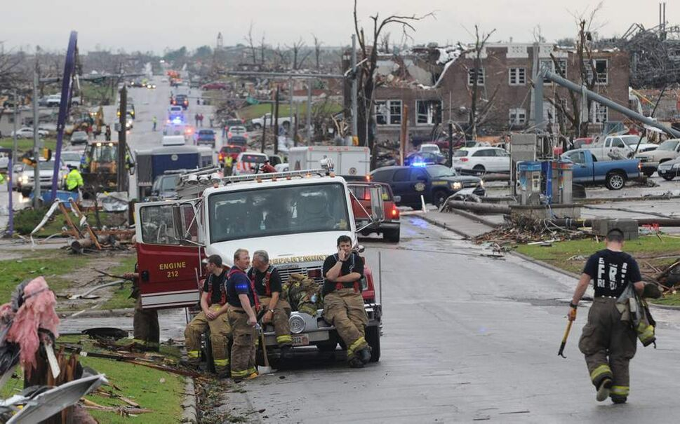 Nevada Missouri firefighters take a break from search and rescue work in Joplin, Mo, on Monday, May 23, 2011. Fire and rescue workers from neighboring cities and states have joined the rescue effort from the tornado that struck Joplin on Sunday, May 22. (AP Photo/Mike Gullett) (CP)