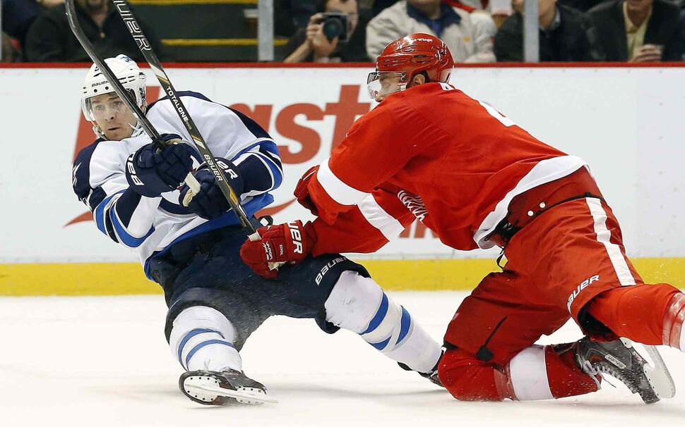 Winnipeg Jets centre Mark Scheifele and Detroit Red Wings defenceman Jakub Kindl collide during the first period. (PAUL SANCYA / THE ASSOCIATED PRESS)