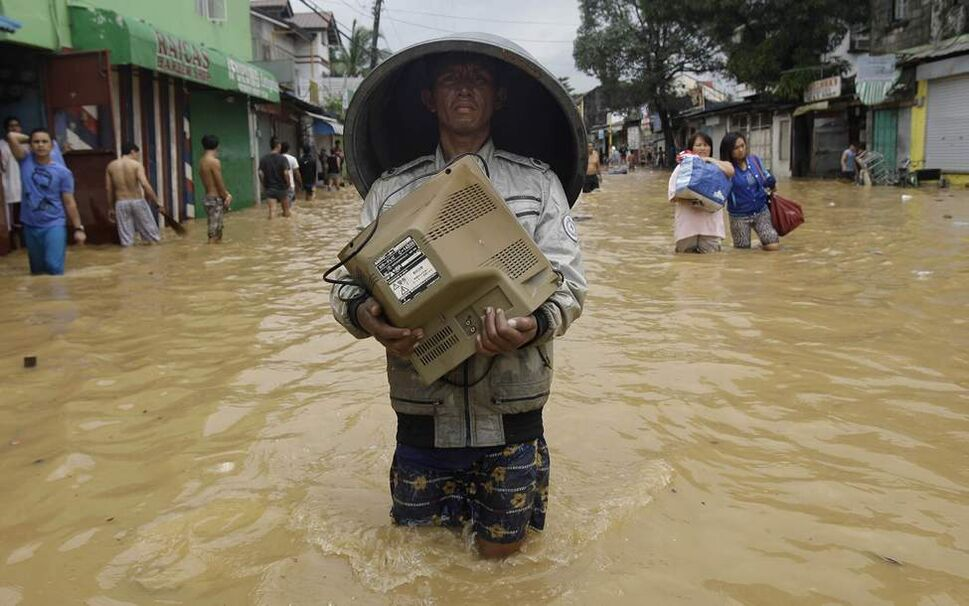 A resident carries a monitor along a flooded road in Marikina City, east of Manila, Philippines, Wednesday Aug. 8, 2012. Widespread flooding battered a million others and paralyzed the Philippine capital began to ease Wednesday as cleanup and rescue efforts focused on a large number of distressed residents, some still marooned on their roofs.  AP Photo / Aaron Favila
