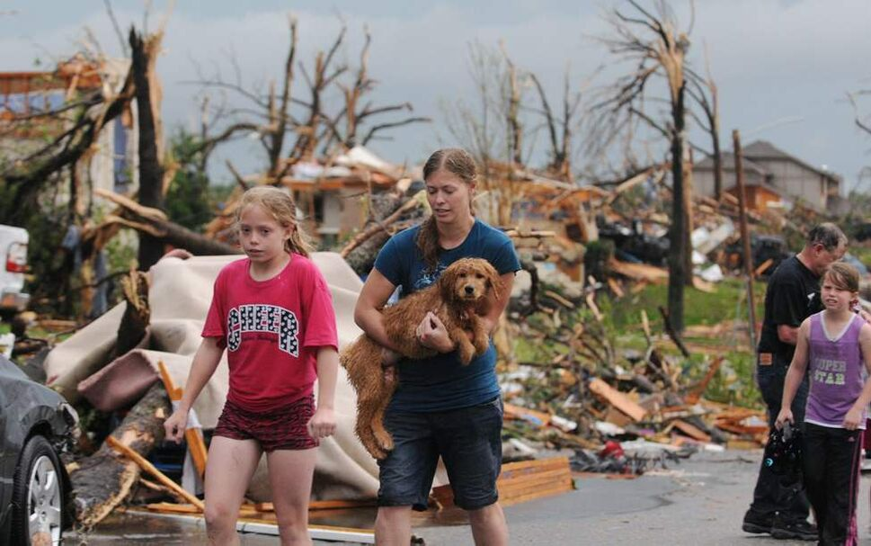 On this Sunday, May 22, 2011 photo, two young Joplin, Mo, residents carry their dog and head to a rescue center after their home was destroyed by a tornado that hit the southwest Missouri city on Sunday evening. The tornado tore a path a mile wide and four miles long destroying homes and businesses. (AP Photo/Mike Gullett) (CP)