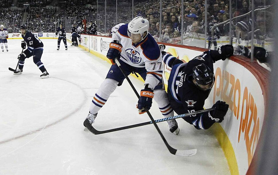 Winnipeg Jets' Andrew Ladd (16) clings to the boards after Edmonton Oilers' Anton Belov (77) takes him down during second period NHL hockey action at MTS Centre in Winnipeg Saturday. (Trevor Hagan / Winnipeg Free Press)
