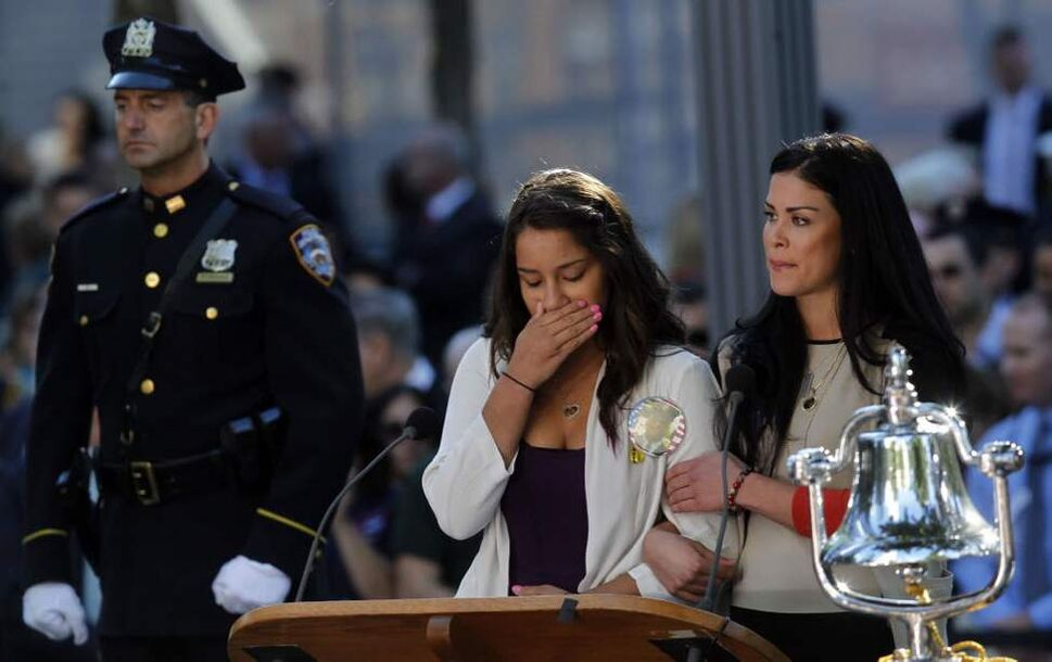 A woman becomes emotional after reading the name of her father as friends and relatives of the victims of 9/11 gather for a ceremony marking the 11th anniversary of the attacks at the National September 11 Memorial at the World Trade Center site in New York. (AP Photo/Jason DeCrow)