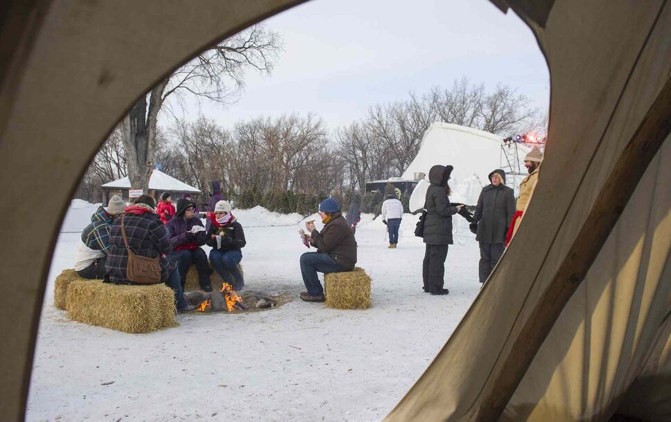 Festival-goers warm up by the fire at Festival du Voyageur on Saturday, Feb. 22. (David Lipnowski / Winnipeg Free Press)