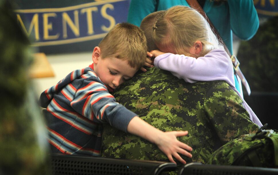 Seven-year-old Alyssa Borkofsky and her little brother four-year-old Reece wrap their arms tightly around their dad, Sergeant Michael Borkofsky, just before leaving for his deployment to Romania at 17 Wing Winnipeg. Borkofsky's family, including his wife, shared hugs and tears along with other service members families that were also headed there to replace members presently engaged in the NATO reassurance Measures Eastern Europe.  (Ruth Bonneville / Winnipeg Free Press  )