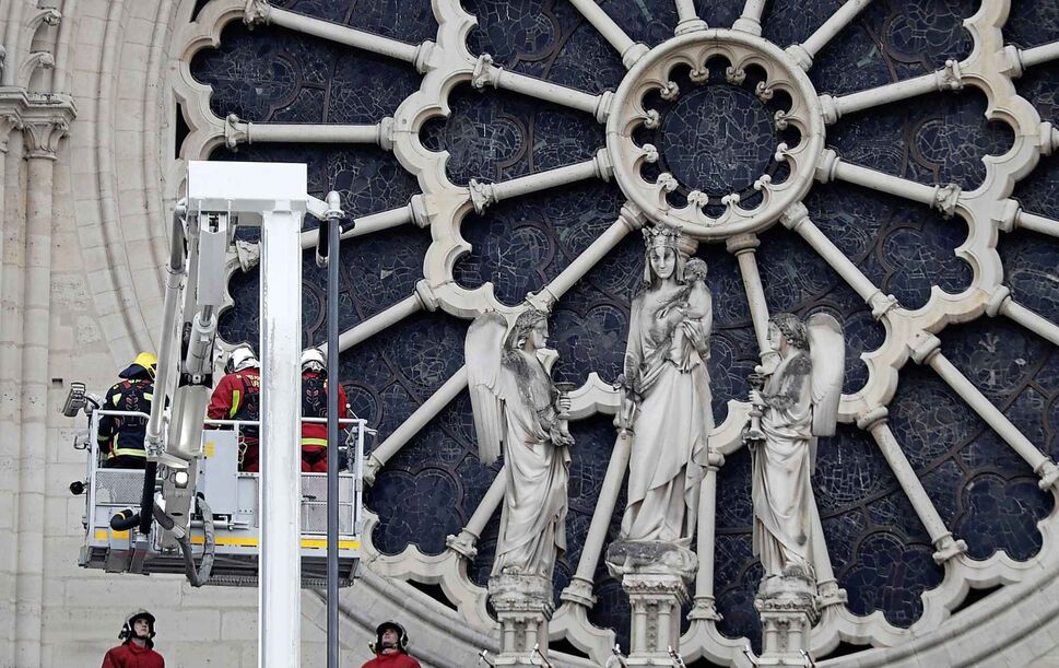 Firefighters work near the rose window of Notre Dame cathedral Tuesday. (Thibault Camus  / The Associated Press)