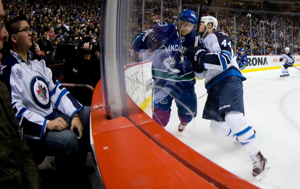 Winnipeg Jets defenceman Zach Bogosian (right) checks Vancouver Canucks' Jannik Hansen into the boards during the first period. (DARRYL DYCK / THE CANADIAN PRESS)