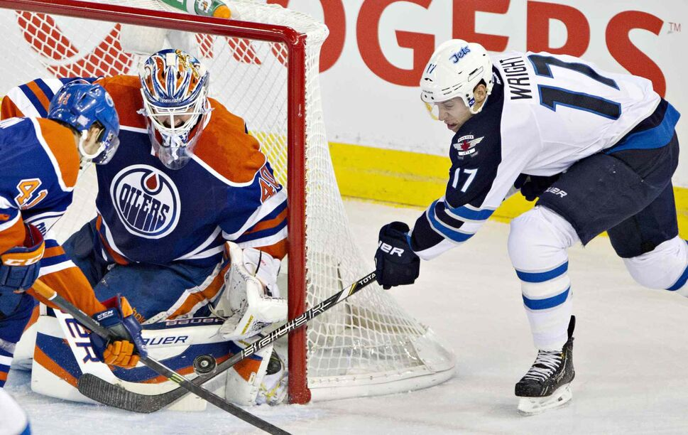 Winnipeg Jets' James Wright (17) is stopped by Edmonton Oilers' Devan Dubnyk (40) as Will Acton (41) chases the rebound during first-period NHL hockey action in Edmonton Tuesday. (Jason Franson / The Canadian Press)