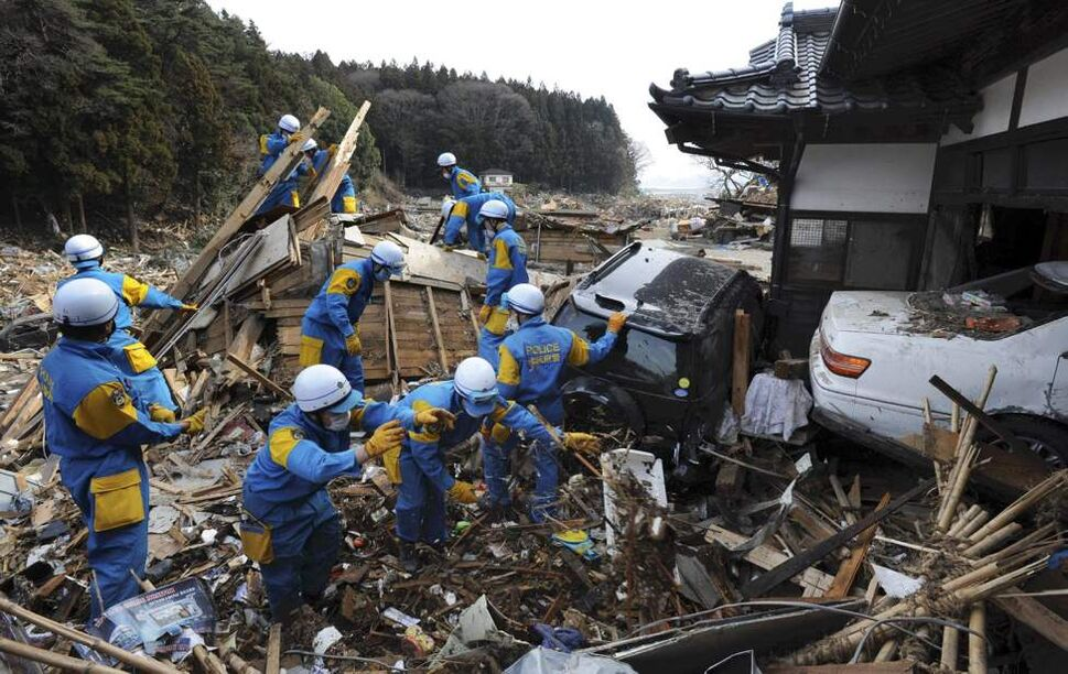 Rescue members seek survivors in Rikuzentakata, northern Japan, Monday, March 14, 2011, three days after a powerful earthquake-triggered tsunami hit the country's east coast. (AP Photo/The Yomiuri Shimbun, Masamine Kawaguchi)