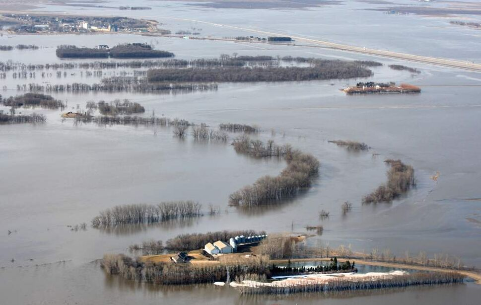 Farmers' properties are surrounded by the flooded Red River north of  of St Jean Baptiste, Manitoba.  The town is located along Highway 75, 40 km north of the United States border. The town of St Jean Baptiste, top, is surrounded by a ring dike keeping it safe from the flood waters. JOE BRYKSA/WINNIPEG FREE PRESS