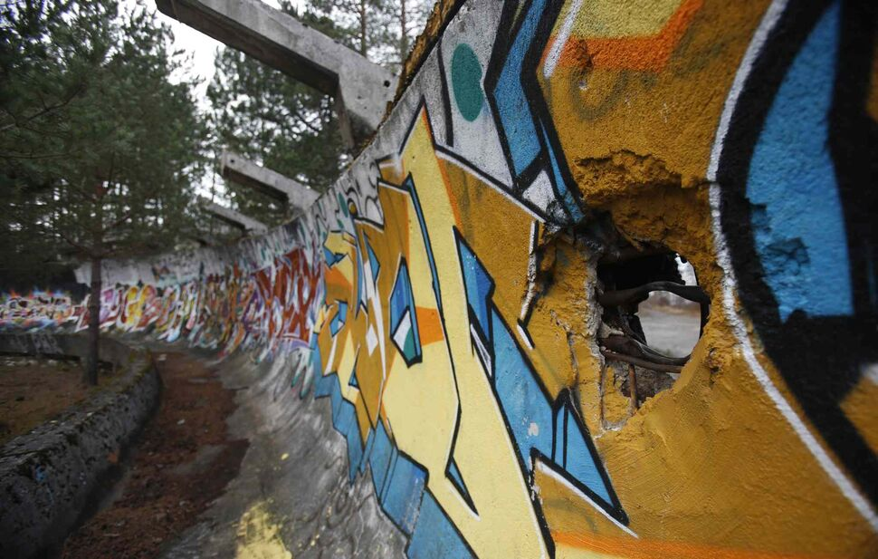 The bobsleigh track damaged by artillery fire is painted with graffiti at Mt. Trebevic near Bosnian capital of Sarajevo. The world came together in the former Yugoslavia in 1984 after the West had boycotted the 1980 Olympics in Moscow and Russia boycotted the 1984 Summer Games in Los Angeles. (Amel Emric / The Associated Press)