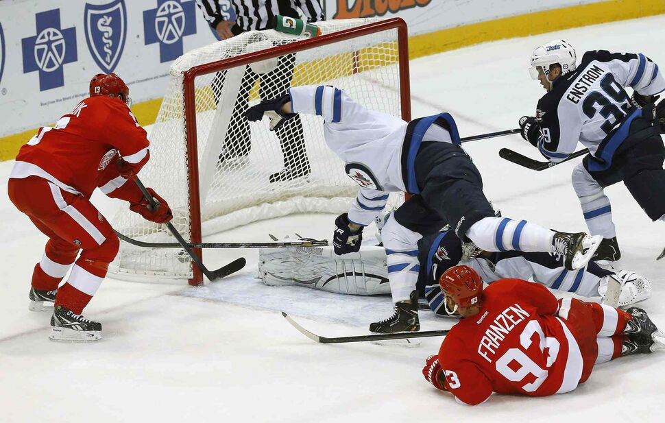 Detroit Red Wings forward Pavel Datsyuk scores a goal on Winnipeg Jets goalie Ondrej Pavelec as Jets forward James Wright tries to defend in the third period. (PAUL SANCYA / THE ASSOCIATED PRESS)