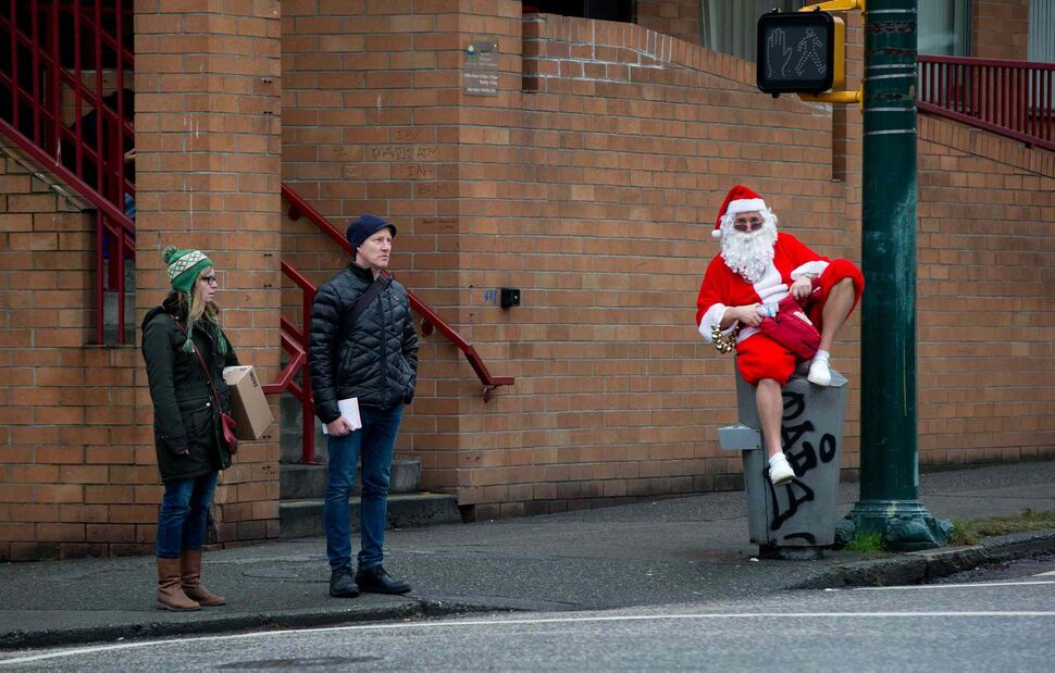A man dressed as Santa Claus sits on a garbage can while waiting for other Santas to gather. (DARRYL DYCK / THE CANADIAN PRESS)