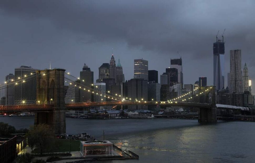 The lights on the Brooklyn Bridge stand in contrast to the lower Manhattan skyline on Tuesday which lost its electrical supply, after megastorm Sandy swept through New York. A record storm surge that was higher than predicted along with high winds damaged the electrical system and plunged millions of people into darkness. (AP Photo/Mark Lennihan)