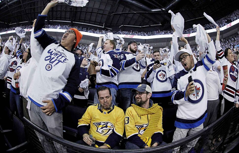 JOHN WOODS / WINNIPEG FREE PRESS</p><p>May 1 — Nashville Predators' fans Ash Greyson, left, and Ryan Dunlap are surrounded by cheering Winnipeg Jets' fans after Jets' Dustin Byfuglien (33) scores during second period NHL round two game three playoff action in Winnipeg.</p>